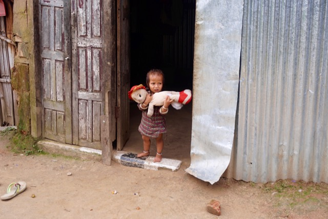A young Nepali girl playing with her doll